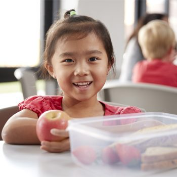 Young Chinese schoolgirl sitting at a table during her lunch break at kindergarten, holding an apple and smiling, close up