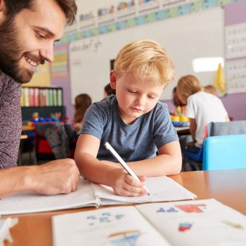 Elementary School Teacher Giving Male Pupil One To One Support In Classroom